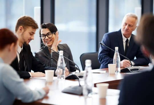 Workers Whispering in Business Meeting