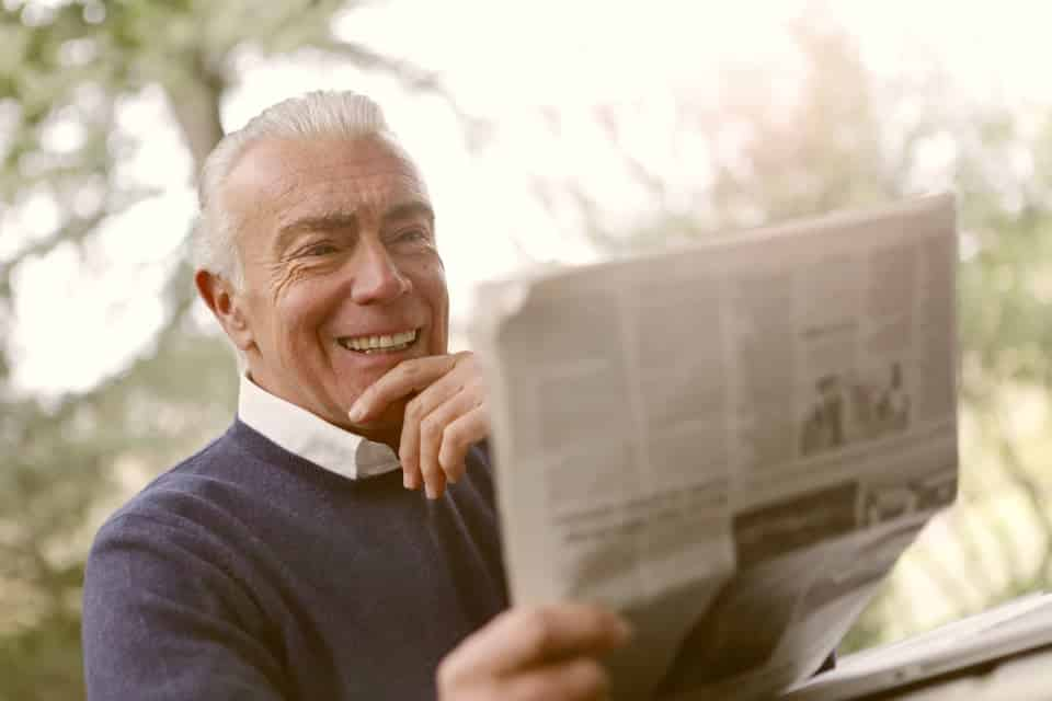 elderly man with newspaper smiling